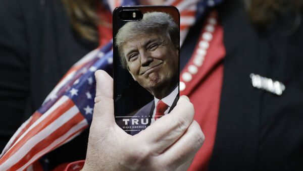 In this Thursday, Sept. 29, 2016, file photo, a woman holds up her cell phone before a rally with then presidential candidate Donald Trump in Bedford, N.H. - Sputnik Türkiye