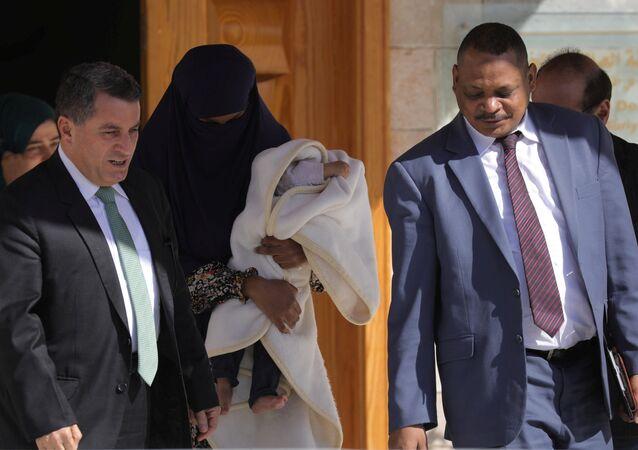 DSG Dış İlişkiler Sorumlusu Abdulkerim Omar (solda), IŞİD mensubu Sudanlı bir kadın ile bir aylık bebeğini, Sudanlı bir diplomata teslim etti.