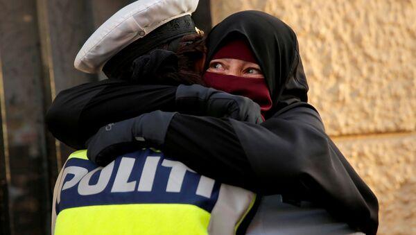 Danimarka'da yürürlüğe giren peçe yasağını protesto eden Ayah adlı eylemciye sarılan kadın polis - Sputnik Türkiye