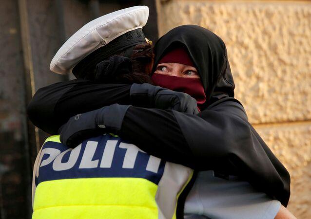 Danimarka'da yürürlüğe giren peçe yasağını protesto eden Ayah adlı eylemciye sarılan kadın polis