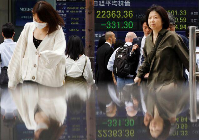 Tokyo Menkul Kıymetler Borsası Nikkei 225 Endeksi panoları önünden geçen Japonlar