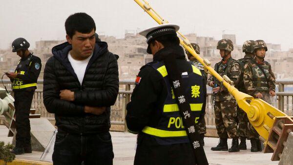 Çin'in Sincan Uygur Özerk Bölgesi'nde polis kimlik denetimi yapıyor. - Sputnik Türkiye