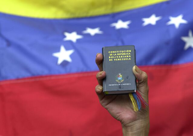 A demonstrator holds up a miniature copy of Venezuela's constitution in front of the nation's flag at a government rally in Caracas, Venezuela, Tuesday, April 13, 2004.