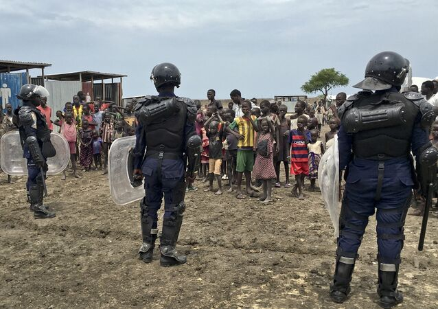 A crowd of displaced people look on as members of the U.N. multi-national police contingent provide security during a visit of UNCHR High Commissioner Filippo Grandi to South Sudan's largest camp for the internally-displaced, in Bentiu, South Sudan Sunday, June 18, 2017