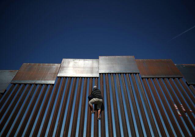 Meksika-ABD sınırındaki çitlere tırmanan bir göçmen