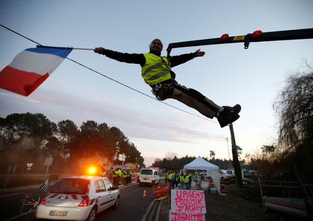 Sarı Yelekler Fransa'nın Cissac-Medoc bölgesinde bir kavşağı işgal edip kontrol noktası kurarken, içlerinden biri vinçten sarkarak elindeki Fransa bayrağıyla  araçları selamladı.