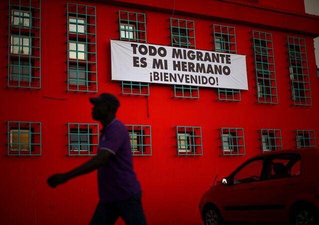 Şili'de Haitili bir göçmen ve Tüm göçmenler kardeşimizdir, Hoşgeldiniz yazılı bir pankart