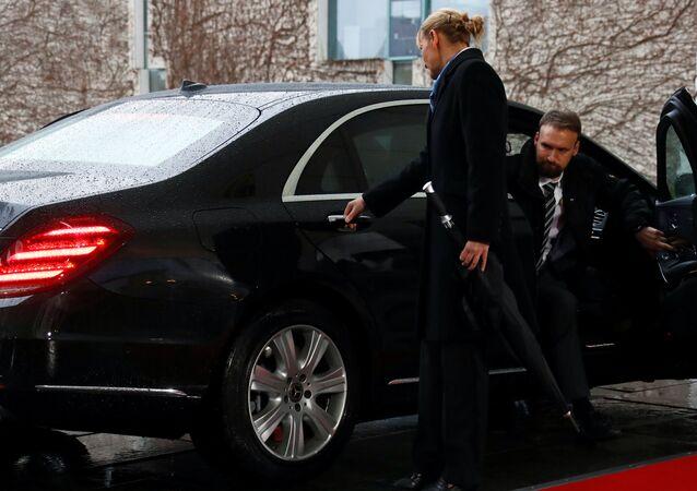 Merkel'in şaşkın bakışları arasında biri kadın biri erkek iki yardımcı kapıyı açabilmek için kolu çekiştirip düğmeleri kurcaladı. Kısa bir uğraşının ardından kapı açıldı ve May dışarı çıktı.