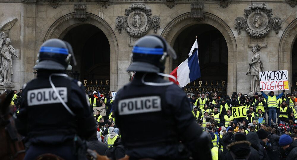 15 Aralık'ta Paris'teki Opera binası önünde atlı polislerin kuşattığı Sarı Yelekler'den biri, Fransa Cumhurbaşkanı Emmanuel Macron'a hitaben Defol git yazılı dövizi havaya kaldırmış halde görülüyor.
