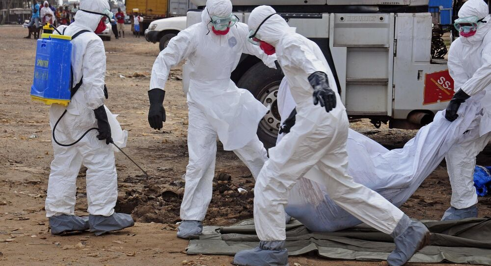 Health workers carry the body of a man suspected of dying from the Ebola virus and left in the street