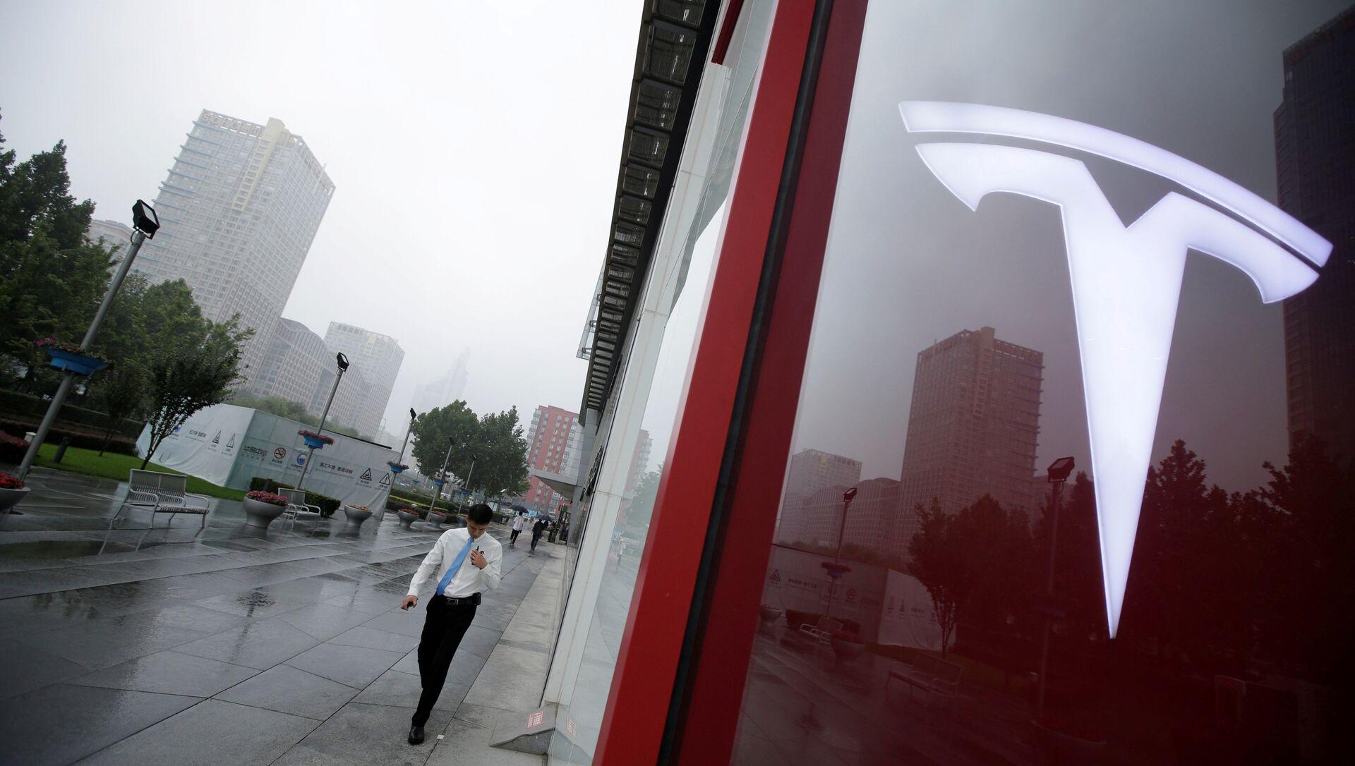 A man walks near a logo of Tesla outside its China headquarters at China Central Mall in Beijing, China July 11, 2018 - Sputnik Türkiye, 1920, 27.04.2021