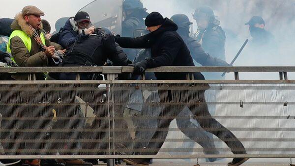 Paris'te Fransız meclisi yakınındaki köprü üzerinde polisin saldırdığı protestocuların imdadına siyah bereli ve eldivenli eki şampiyon boksör Christophe Dettinger yetişti. - Sputnik Türkiye
