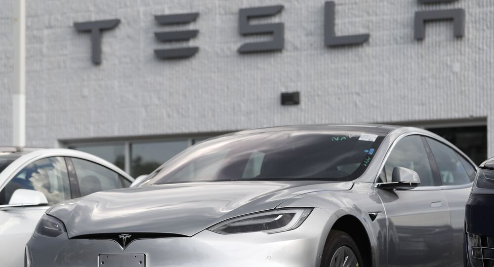 In this Sunday, July 8, 2018, photograph, 2018 Model 3 sedans sit on display outside a Tesla showroom in Littleton, Colo