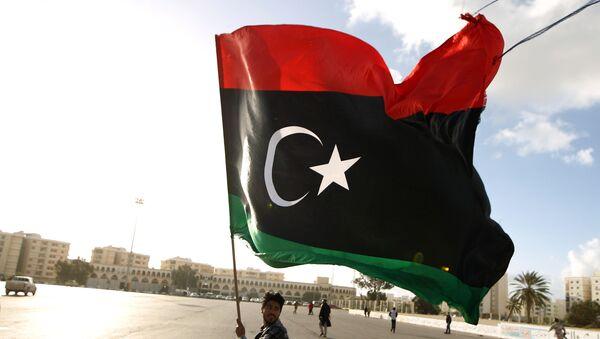 A Libyan man waves a national flag - Sputnik Türkiye