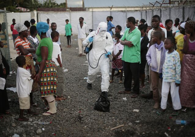 In this file photo daetd Tuesday, Sept. 30, 2014, a medical worker sprays people being discharged from the Island Clinic Ebola treatment center in Monrovia, Liberia