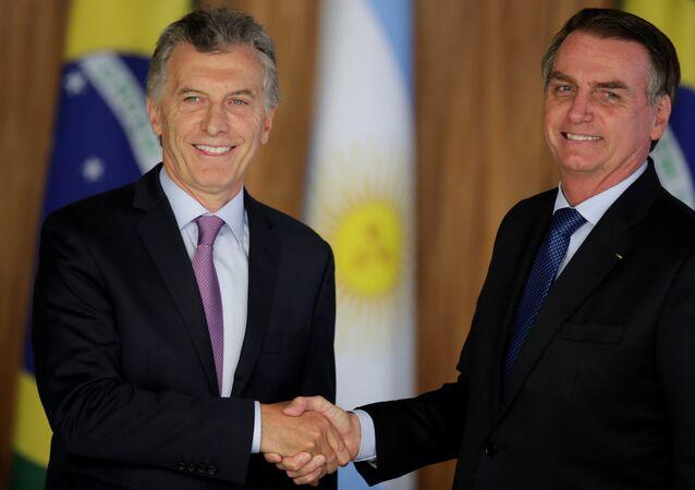 Mauricio Macri  ile Jair Bolsonaro (sağda) Brezilya'daki görüşmede el sıkışırken