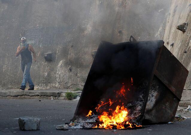 Caracas'ta isyan girişiminde bulunan askeri birliğe yakın Cotiza mahallesinde yaşayanlar tencere tava çalıp çöp konteynerlerini ateşe verdi ve güvenlik güçlerine taş attı.