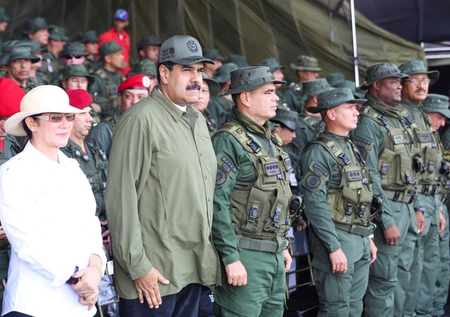 Venezuela's President Nicolas Maduro (2nd L) attends a military parade, as he is flanked by his wife Cilia Flores (L) and Venezuela's Defence Minister Vladimir Padrino Lopez (C), in Maracay, Venezuela September 26, 2017