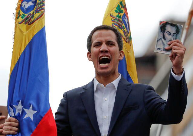 Marcos Perez Jimenez diktatörlüğünün sona ermesinin 61. yıldönümünde kendini 'devlet başkanı' ilan eden Juan Guaido, elinde Simon Bolivar'ın resminin olduğu Venezüella anayasasıyla