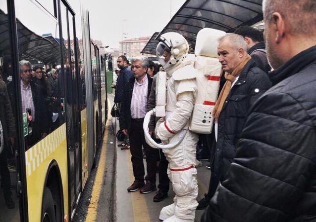 astronot kıyafeti ile metrobüs durağında bekleyen bir vatandaş