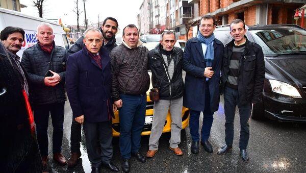 """Ticari taksi sürücüsünün sosyal medyadan yaptığı davet sonrasında taksi durağına sürpriz ziyaret gerçekleştiren CHP'nin İstanbul Büyükşehir Belediye Başkan Adayı Ekrem İmamoğlu'nun, bindiği taksinin camını açıp, """"Beni belediyeye Saraçhane'ye bırakıp gelecek"""" demesi çevredeki vatandaşları güldürdü. - Sputnik Türkiye"""