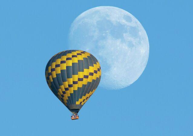 A hot air balloon floats past an almost full rising moon on a warm fall evening near Encinitas, California October 5, 2014.