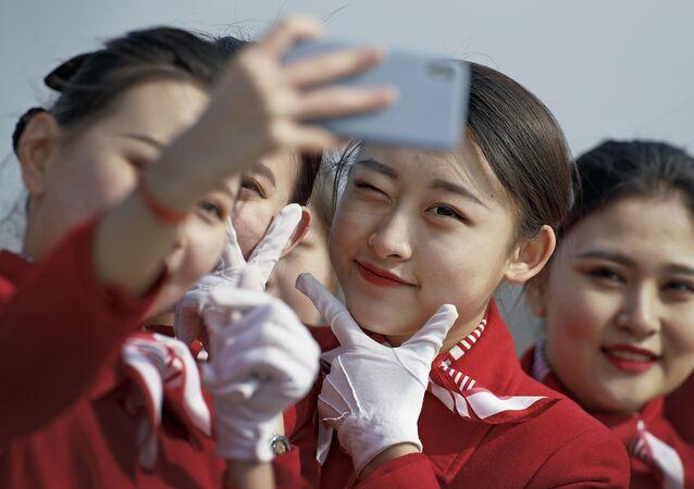 Pekin'de düzenlenen Çin Ulusal Halk Kongresi'nin (ÇUHK) oturumlarına katılan delegeleri karşılayan ulusal kıyafetli hostes kızları.