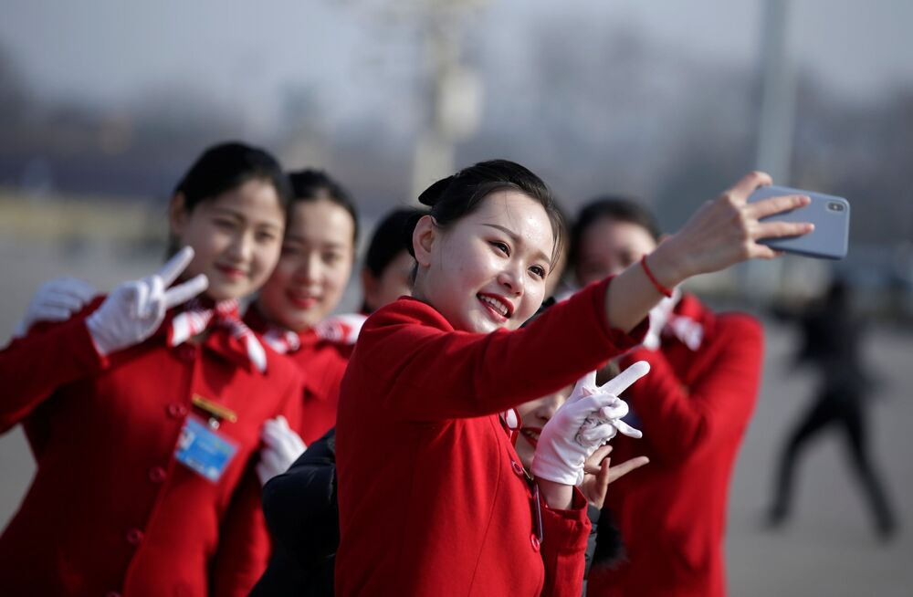 Pekin'deki etkinliğe katılan hostes kızları selfie çekiyor.