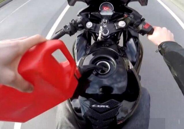 seyir halinde deposuna benzin dolduran motosiklet sürücüsü