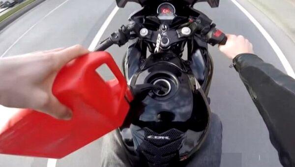seyir halinde deposuna benzin dolduran motosiklet sürücüsü - Sputnik Türkiye