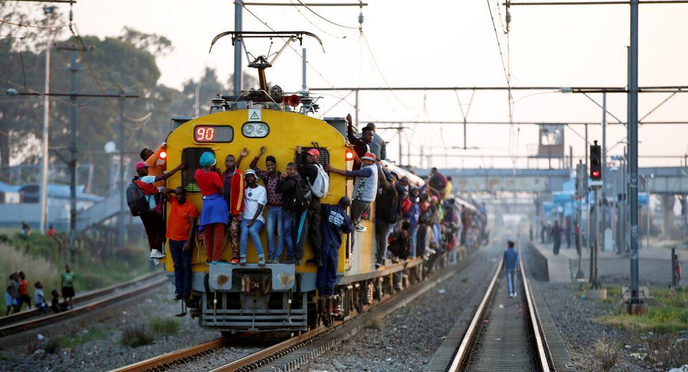 Güney Afrika'nın Soweto kentinde iş dönüşü banliyö trenine asılarak yolculuk
