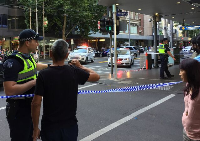 Police officers stand guard as members of the public stand behind police tape after the arrest of the driver of a vehicle that ploughed into pedestrians at a crowded intersection near the Flinders Street train station in central Melbourne, Australia December 21, 2017