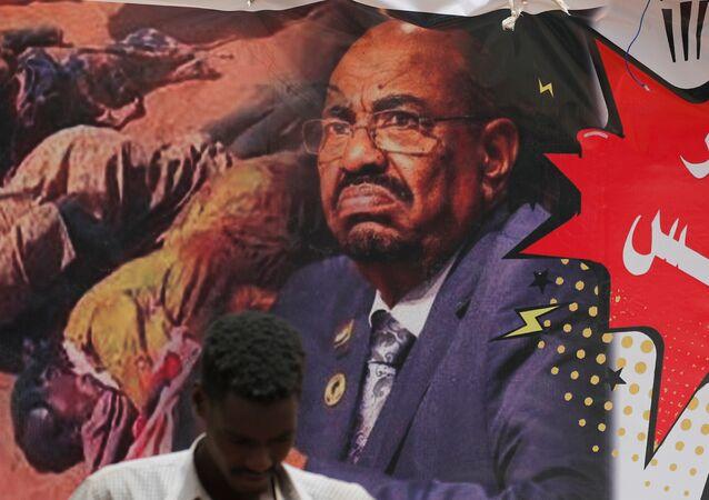 Sudan'da bir gösterici devrik lider Ömer Beşir'in posterinin önünde duruyor