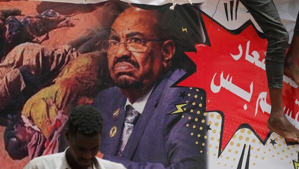 Sudan'da bir gösterici devrik lider Ömer Beşir'in posterinin önünde duruyor - Sputnik Türkiye