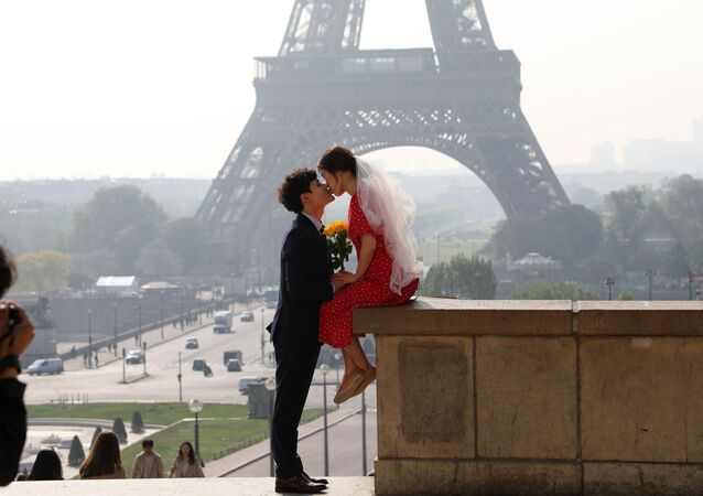 A couple kiss at the Trocadero overlooking the Tour Eiffel in Paris on April 30 2019. (Photo by Ludovic MARIN / AFP)