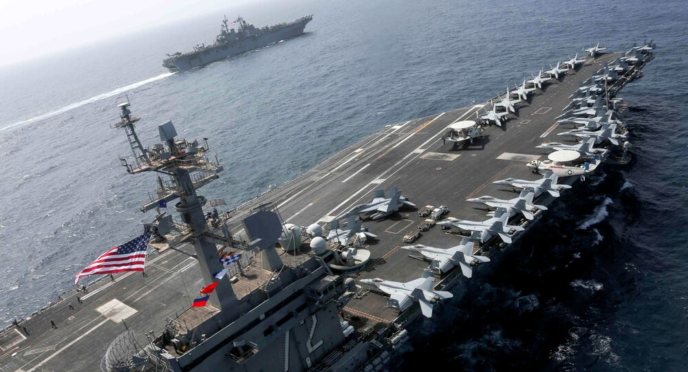 The Nimitz-class aircraft carrier USS Abraham Lincoln (CVN 72) and the Wasp-class Amphibious Assault Ship USS Kearsarge (LHD 3) sail alongside, as the Abraham Lincoln Carrier Strike Group (ABECSG) and Kearsarge Amphibious Ready Group (KSGARG) conduct joint operations, in the U.S. 5th Fleet area of operations in the Arabian Sea, May 17, 2019. Picture taken May 17, 2019. Mass Communication Specialist 1st Class Brian M. Wilbur/U.S. Navy/Handout via REUTERS ATTENTION EDITORS - THIS IMAGE HAS BEEN SUPPLIED BY A THIRD PARTY.