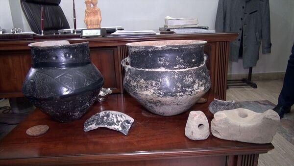Erzurum'un Aziziye ilçesi Söğütlü köyünde, traktörle tarlasını süren Mesut Küçük, pulluğa takılan taşın altında5 bin yıllık çömlek, taş ocak ve ağırlıklardan oluşan 5 ayrı tarihi eser buldu. - Sputnik Türkiye