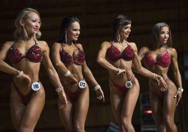 Kazakistan'ın başkenti Nursultan'da düzenlenen Asya Vücut Geliştirme Şampiyonası'nın kadın katılımcıları podyumda.