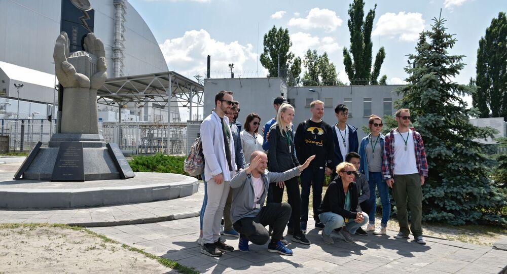 1986'da korkunç facianın yaşandığı Çernobil'e düzenlenen tur sırasında Çernobil nükleer santralinde patlamanın sonuçlarının bertaraf edilmesine yönelik çalışmalara katılanların anısına dikilen anıtın yanında fotoğraf çeken turistler.
