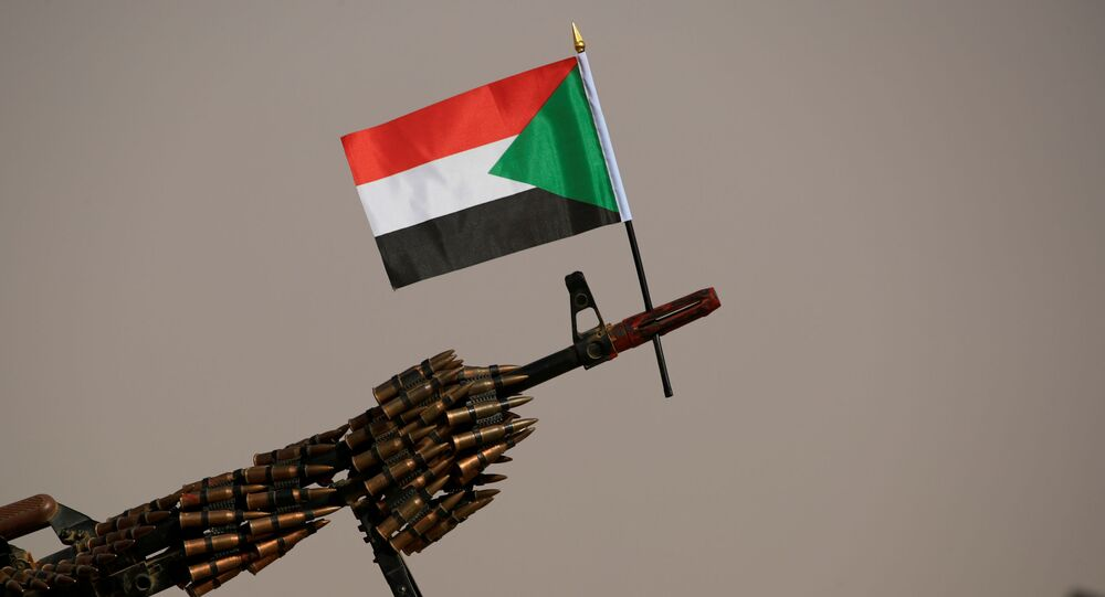 FILE PHOTO: A Sudanese national flag is attached to a machine gun of Paramilitary Rapid Support Forces (RSF) soldiers as they wait for the arrival of Lieutenant General Mohamed Hamdan Dagalo, deputy head of the military council and head of RSF, before a meeting in Aprag village 60, kilometers away from Khartoum, Sudan, June 22, 2019. REUTERS/Umit Bektas/File Photo
