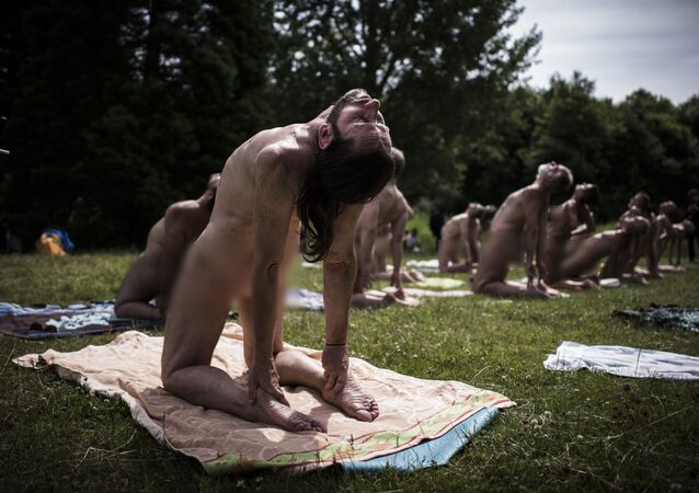 EDITORS NOTE: Graphic content / Naturists practice yoga in the Bois de Vincennes on the outskirts of Paris on June 24, 2018. (Photo by Philippe LOPEZ / AFP)