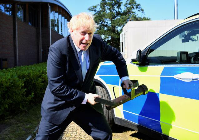 Boris Johnson, a leadership candidate for Britain's Conservative Party, holds a battering ram as he visits the Thames Valley Police Training Centre in Reading, Britain, July 3, 2019. REUTERS/Dylan Martinez/Pool
