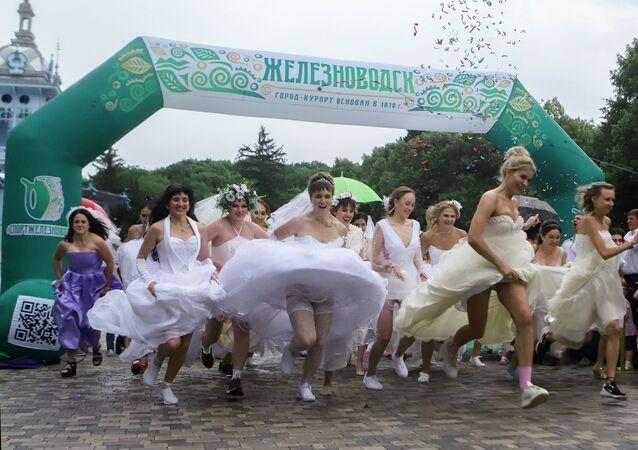 Gelin Yarışları için yarışan gelinlikli kadınlar.