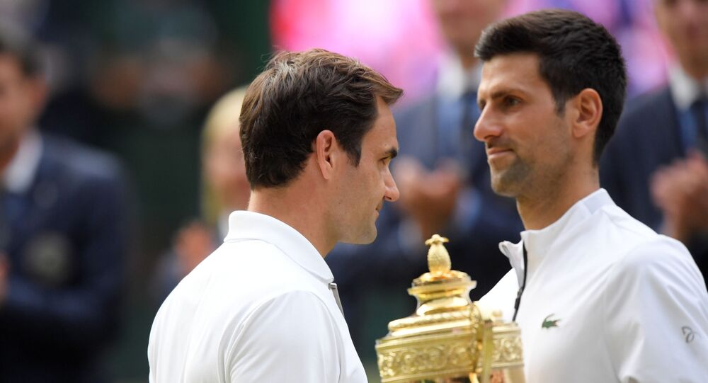 Tennis - Wimbledon - All England Lawn Tennis and Croquet Club, London, Britain - July 14, 2019  Serbia's Novak Djokovic poses with the trophy after winning the final as Switzerland's Roger Federer looks on   REUTERS/Toby Melville