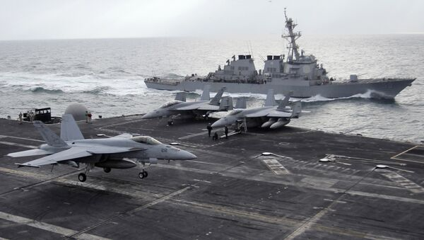 This file photo taken on Monday, Feb. 13, 2012 shows a U.S. F-18 fighter jet, left, land on the Nimitz-class aircraft carrier USS Abraham Lincoln (CVN 72) as a U.S. destroyer sells on alongside during fly exercises in the Persian Gulf - Sputnik Türkiye