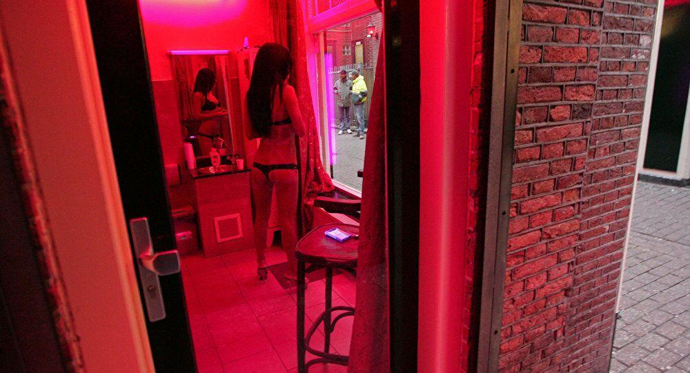 Amsterdam'ın Red Light bölgesinde bir seks işçisi vitrin gibi kullanılan pencerenin gerisinden kendini sergileyerek müşteri bekliyor.