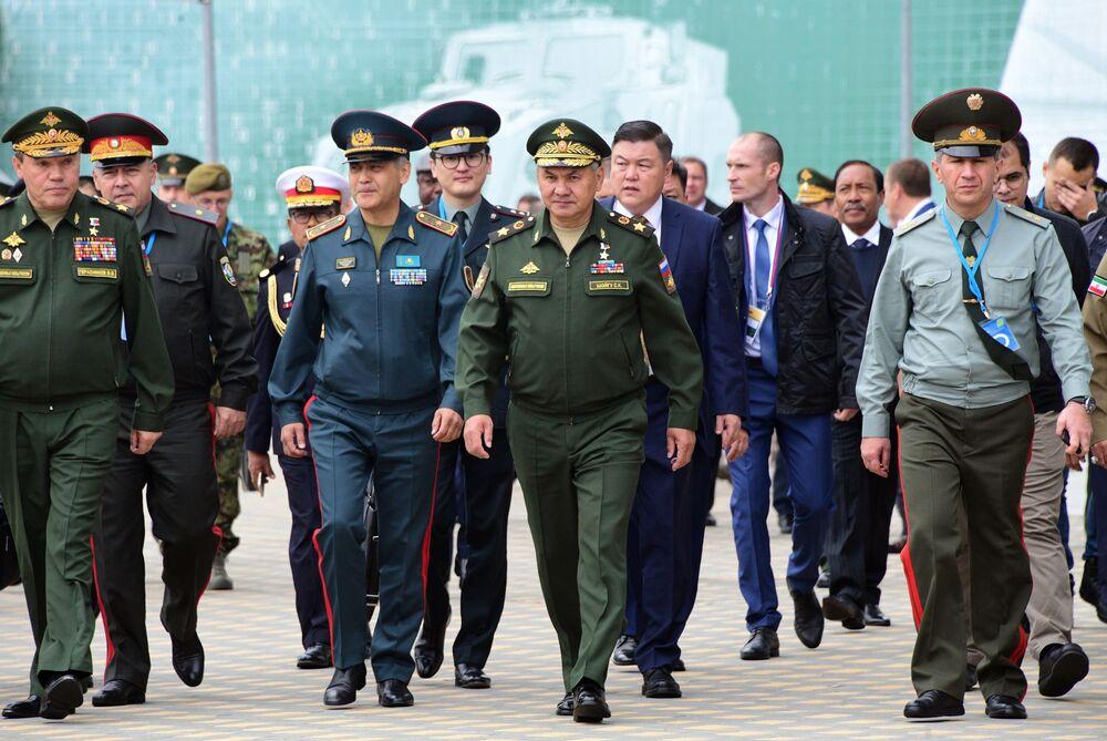 """5 yıl önce uluslararası düzeyde ordu oyunlarını başlatma kararının doğruluğuna dikkat çeken Savunma Bakanı Şoygu (ortada), """"Şu anda oyunlar dünya çapında önem kazandı, her yıl giderek daha popüler hale geliyor ve tutkulu hayranları oluyor. İki hafta boyunca 10 ülke topraklarında yapılacak oyunlarda 39 ülkeden katılan en iyi askeri uzmanlar nefes kesici yarışmalarda ustalıklarını sergileyecek' ifadelerini kullandı."""
