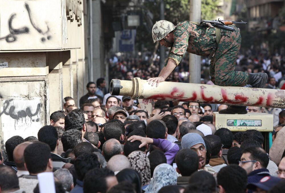 Mısırlı asker, başkent Kahire'nin Tahrir Meydanı'nda refomların yapılması ve Cumhurbaşkanı Hüsnü Mübarek'in istifası talebiyle protesto yapan göstericilerle konuşuyor.