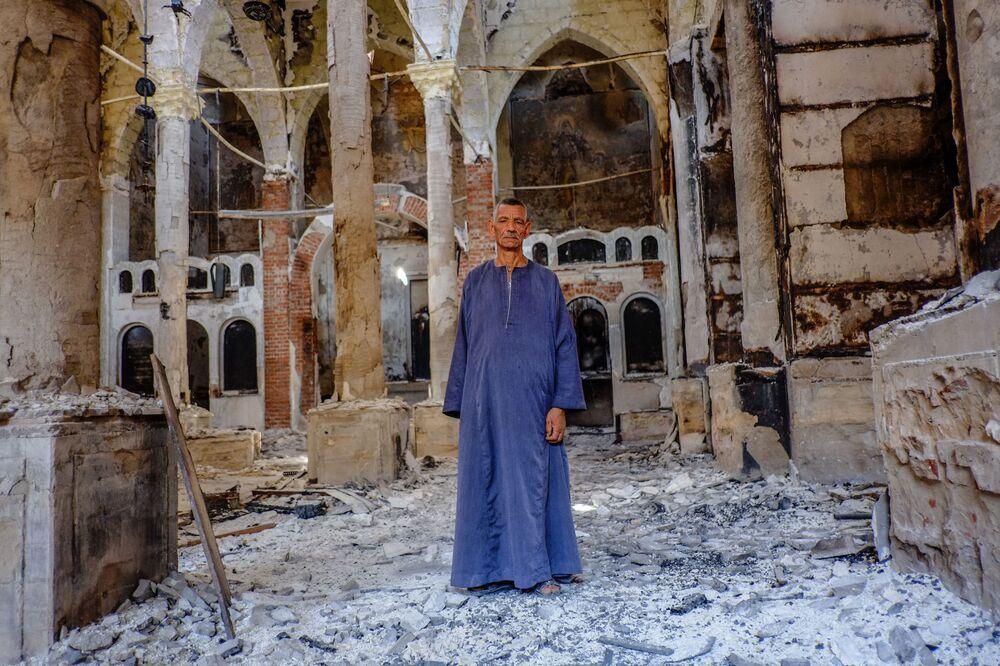 Minya eyaletinde yakılmış kiliselerden birindeki bir Kıpti.  Mısır'da 2013 yılında yaşanan çatışmalarda onlarca kilise yakılıp yıkıldı.