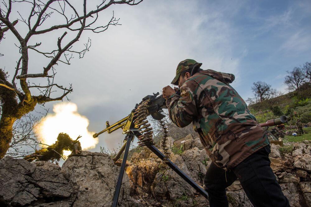 Suriye hükümet güçlerinden Kesab kentinin çevresindeki militanların mevzilerine makineli tüfek atışı, Nisan 2014.